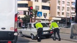 Trafik polisleri, yolda kalan sürücüye, aracını iterek yardım etti